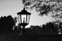 Classic styled outdoor gate lantern highlighted by sunlight at dawn  Silhouette  Black and White