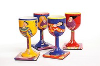 Four hand painted porcelain goblets on matching coasters featuring maidens  Isolated