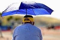 Older man looking at a racing bike and giving shade umbrella