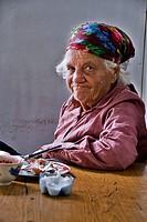 Old, poor woman eating in a food stall  Bishkek, Kyrgyzstan