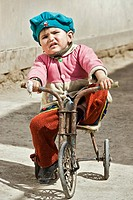 Young girl on her tricycle looking to the camera, Khiva, Uzbekistan, Asia