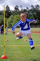 Boy doing the hurdles at a junior soccer tournament, Baden-Wuerttemberg, Germany, Europe