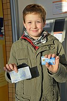 8-year-old boy with his own ec-card at a cash machine, Germany, Europe