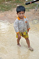 Little boy running through a rain puddle, slums of Siem Reap, Cambodia, Asia