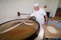 Making Kataifi in the traditional way on a spinning hot plate  Kataifa is a fine stringy filo pastry used in many Greek sweets and desserts, Rethymno,...