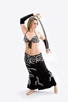 Beautiful belly dancer in black outfit holding sword, isolated