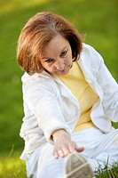 Retired woman in tracksuit stretching outdoors _ healthy lifestyle