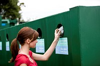 A teenage girl recycling a glass bottle
