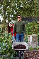 A young couple pushing a wheelbarrow on an allotment