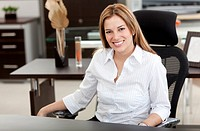 business woman at the office sitting on her desk and smiling