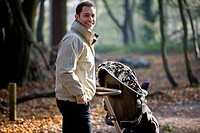 A young father pushing a stroller in the park