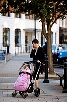 A mother standing with a stroller in the street, talking on her mobile phone