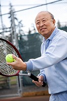 A shot of an senior asian man playing tennis