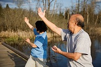 A shot of a senior asian couple doing tai_chi exercise