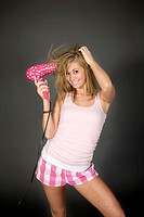 Teenage girl posing on gray background with some attitude and a blowdryer