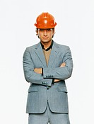Mid adult man in grey suit in orange hard hat