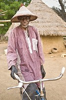 Old Bassari man with funny hat and bicycle looking to the camera, Village of Ibel, Bassari country, Senegal, Africa
