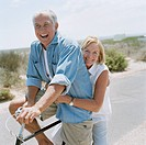 Portrait of senior couple riding bicycle