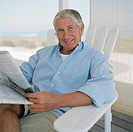 Portrait of senior man sitting in sun lounger, reading newspaper