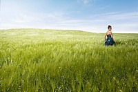 young woman standing in field of reeds, computer_generated