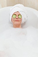 Relaxed woman taking a bath with a towel on her head
