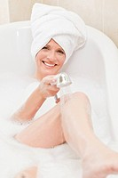 Smiling woman taking a bath with a towel on her head