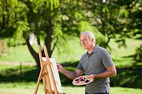 Senior man painting in the garden