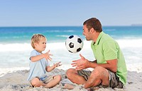 Happy father playing football with his son