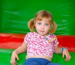 blond little girl resting on colorful playground red and green