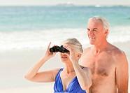 Elderly couple bird watching at the beach