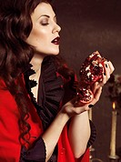 Beautiful woman holding a pomegranate in her hands
