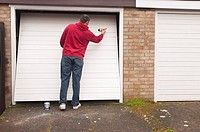 A man doing DIY painting a garage door in the Uk