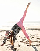 Girl doing cartwheels on the beach