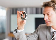 Businessman looking at cog
