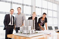Business people standing with building model