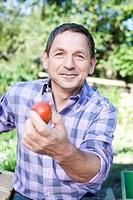 Germany, Saxony, Mature man showing tomato, portrait