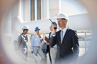 Businessman in hard_hat talking on walkie_talkie outdoors