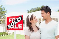 Couple standing near sold sign of their new house (thumbnail)