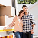 Couple standing together by moving van