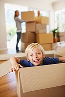 Smiling boy playing on box in new house
