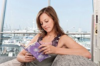 Germany, Hamburg, Woman reading book with harbor in background