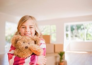 Girl hugging teddy bear in new house