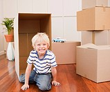 Grinning boy playing with boxes in new house