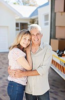 Couple hugging near moving van and new house