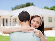 Couple hugging with keys to new house