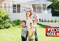 Family standing in front yard of new house next to sold sign
