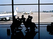 Silhouettes of passengers sitting in airport lounge