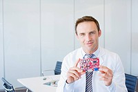 Businessman holding circuit board in office