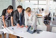 Business people reviewing blueprints together in office