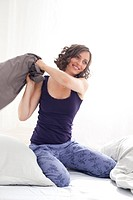 Germany, Leipzig, Young woman playing with pillow, smiling